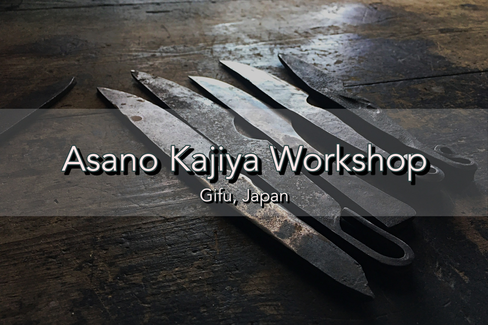Five hand forged knives on a rustic wooden table crafted by master sword smith Fusataro. Text overlay reads Asano Kajiya Workshop Gifu, Japan.