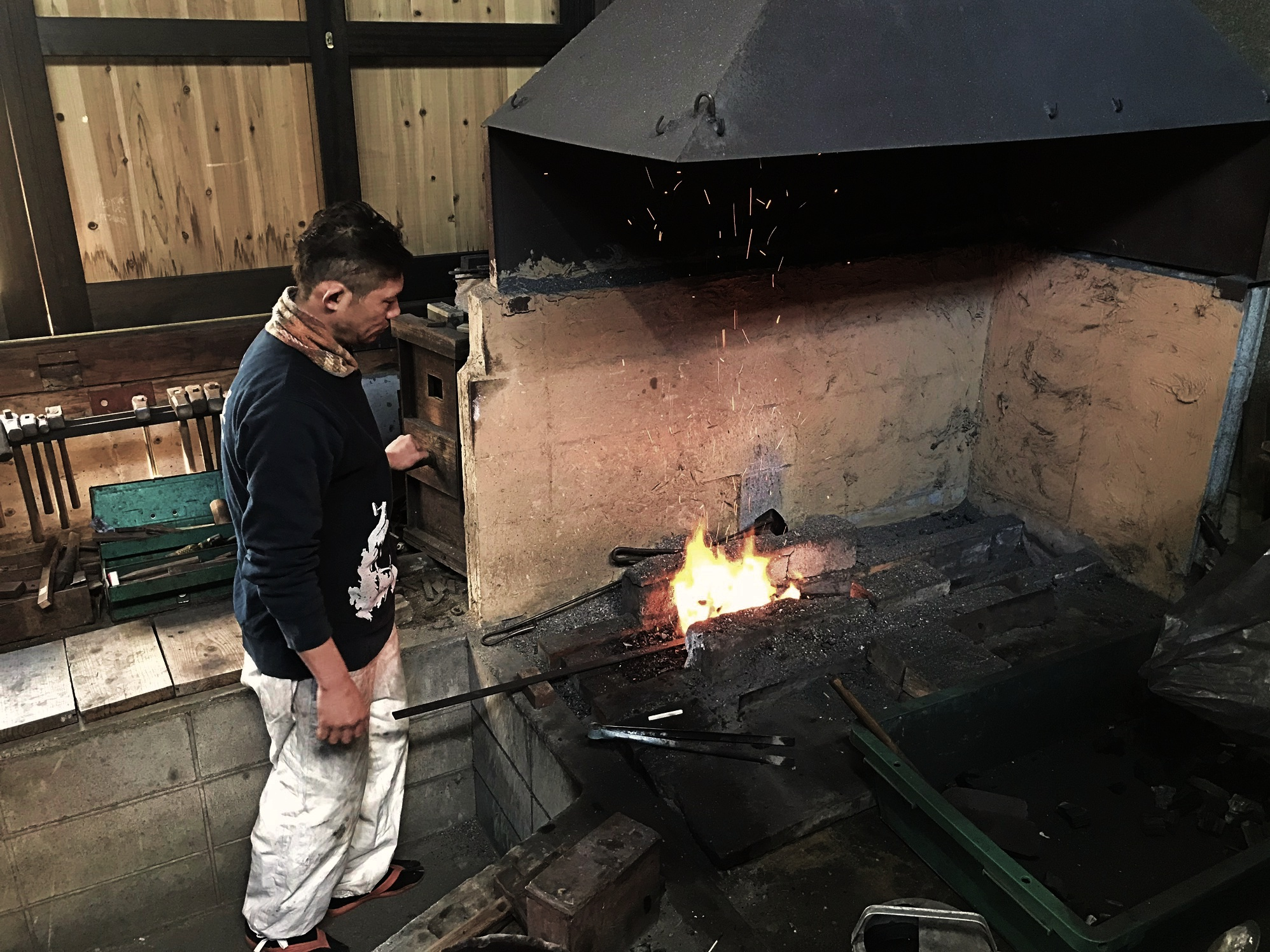Japanese blacksmith pumps air into a forge full of coal by way of an antique wood bellow.