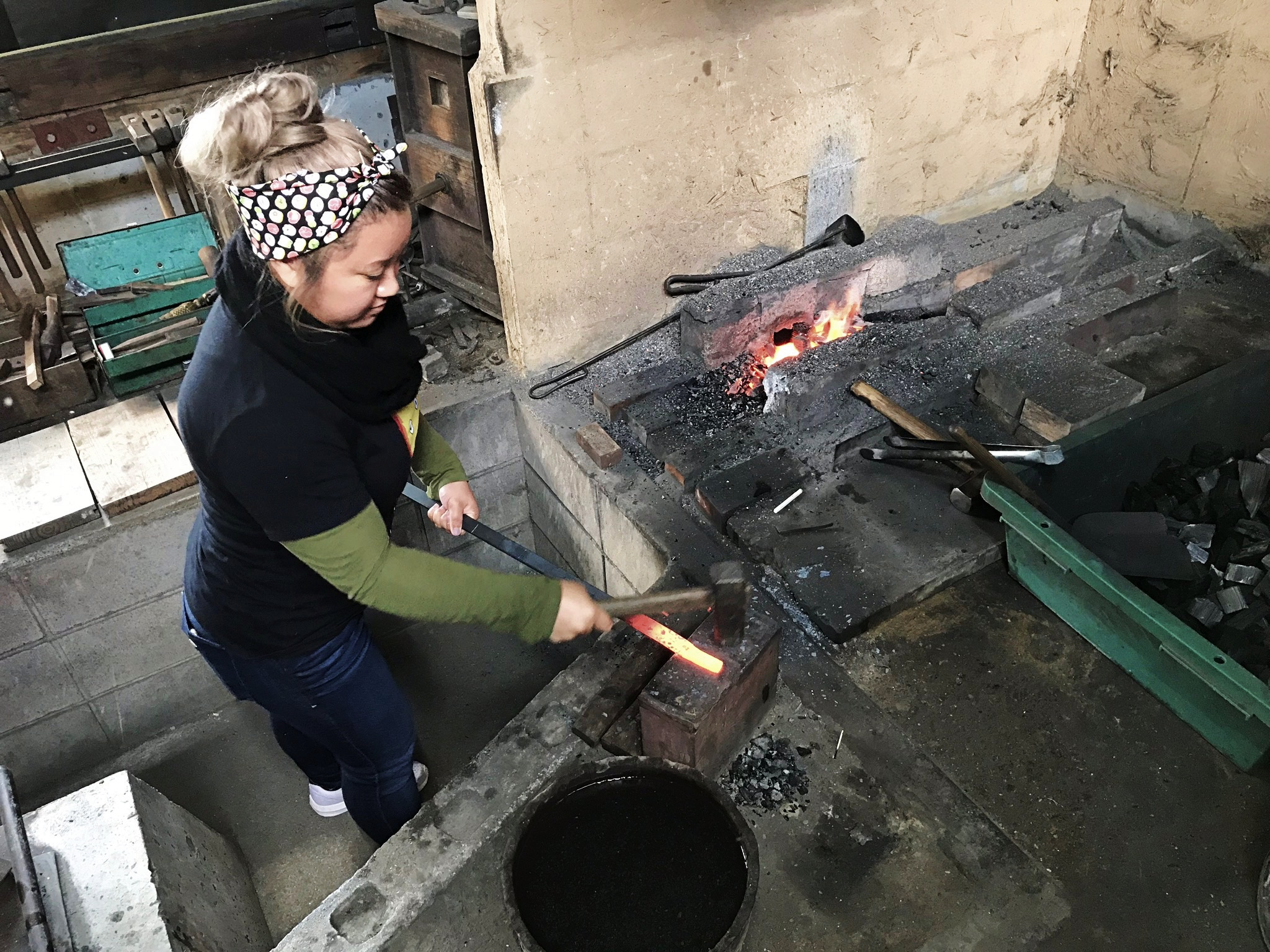 Young woman wearing long sleeves hammers a heated length of metal against an anvil with a stone forge in the background. Her hair is in a bun with a japanese cotton print scarf tied around her head.
