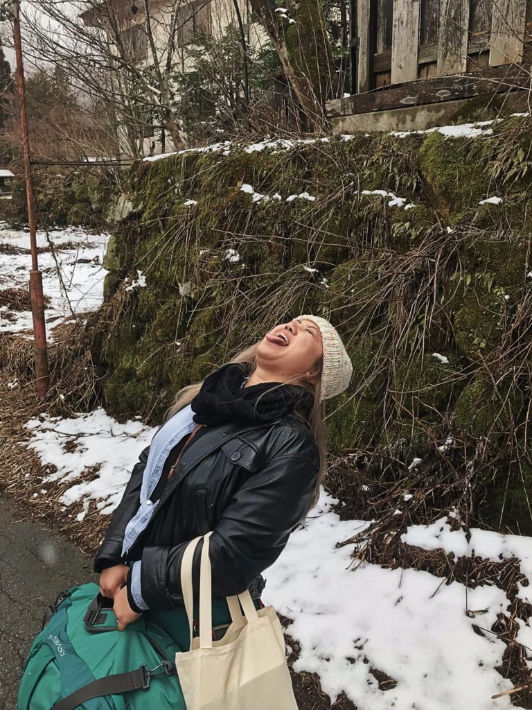 young lady in white beanie, black leather jacket and green emerald skirt catching snowflakes on a snowy road
