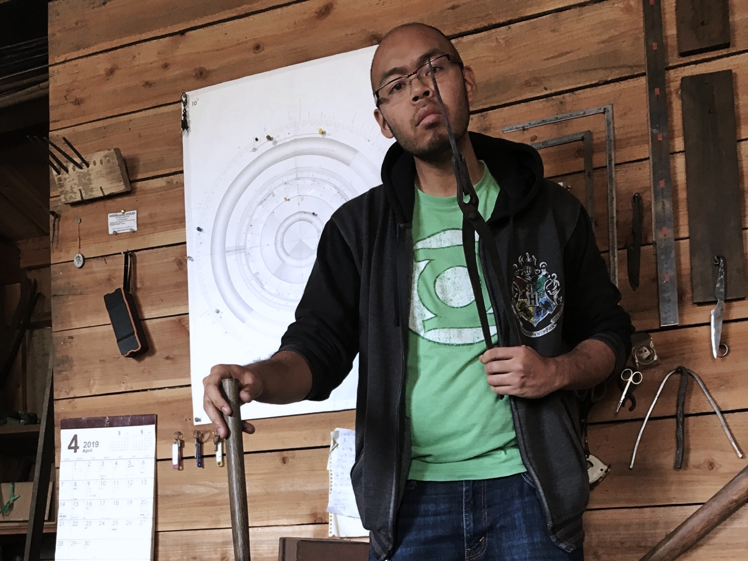 Young man wearing glasses and green lantern t-shirt holds unfinished knife up with metal pliers checking to see if blade is stretched to proper length.