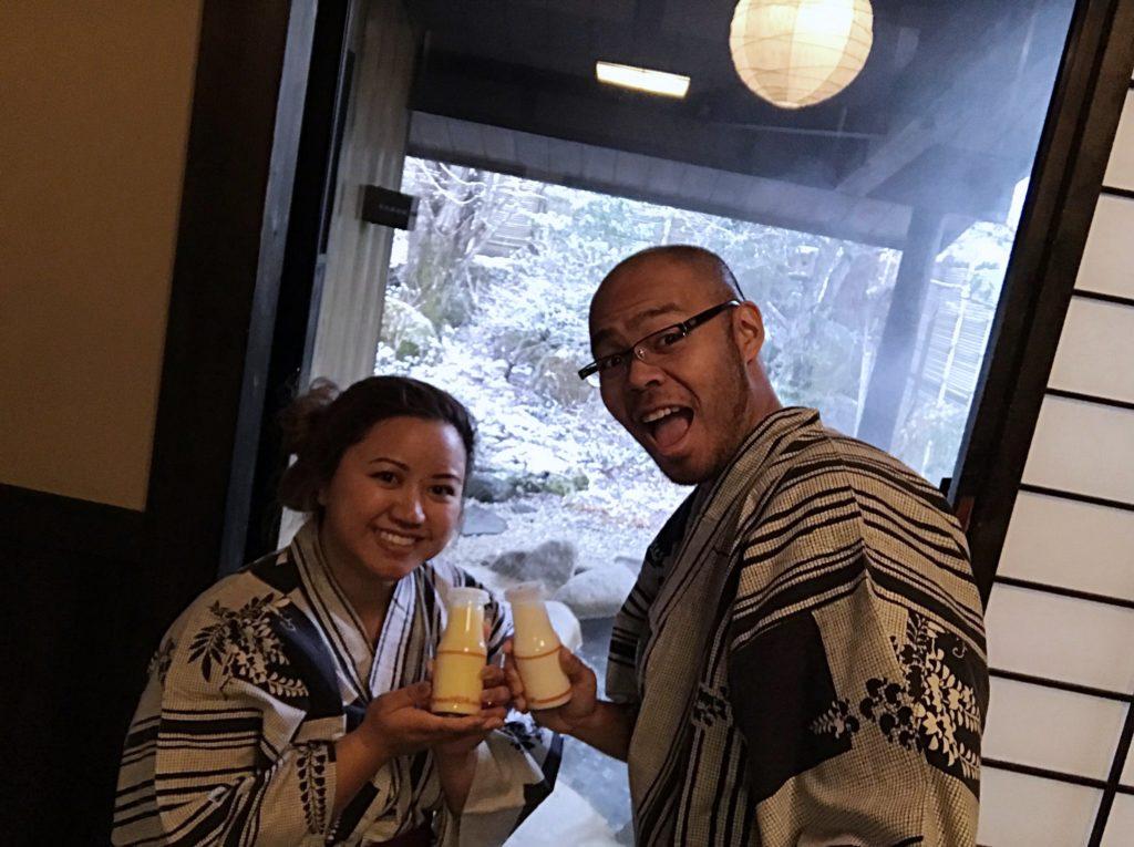 young woman and man with glasses dressed in yukata or japanese kimono holding two small bottles of hida milk with a snowfallen backdrop compliments of Kakurean Hidaji ryokan in takayama japan