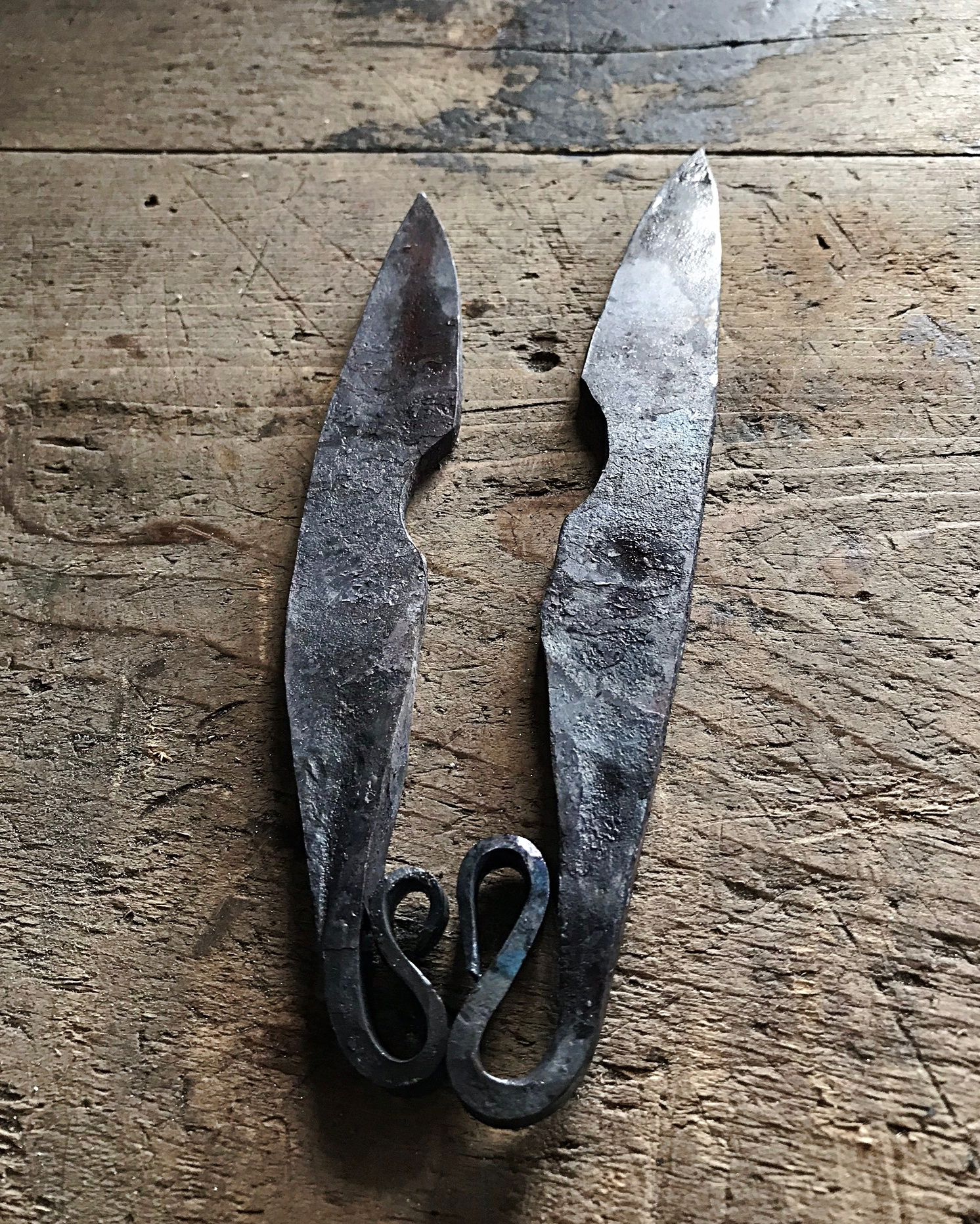 Two unfinished knives with snake tail handles forming a heart shape placed side by side on a wooden table.