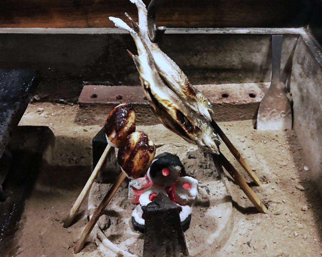 skewers of caramelized mochi and grilled fish roasting above a charcoal pit. kaiseki at Kakurean Hidaji ryokan in takayama japan