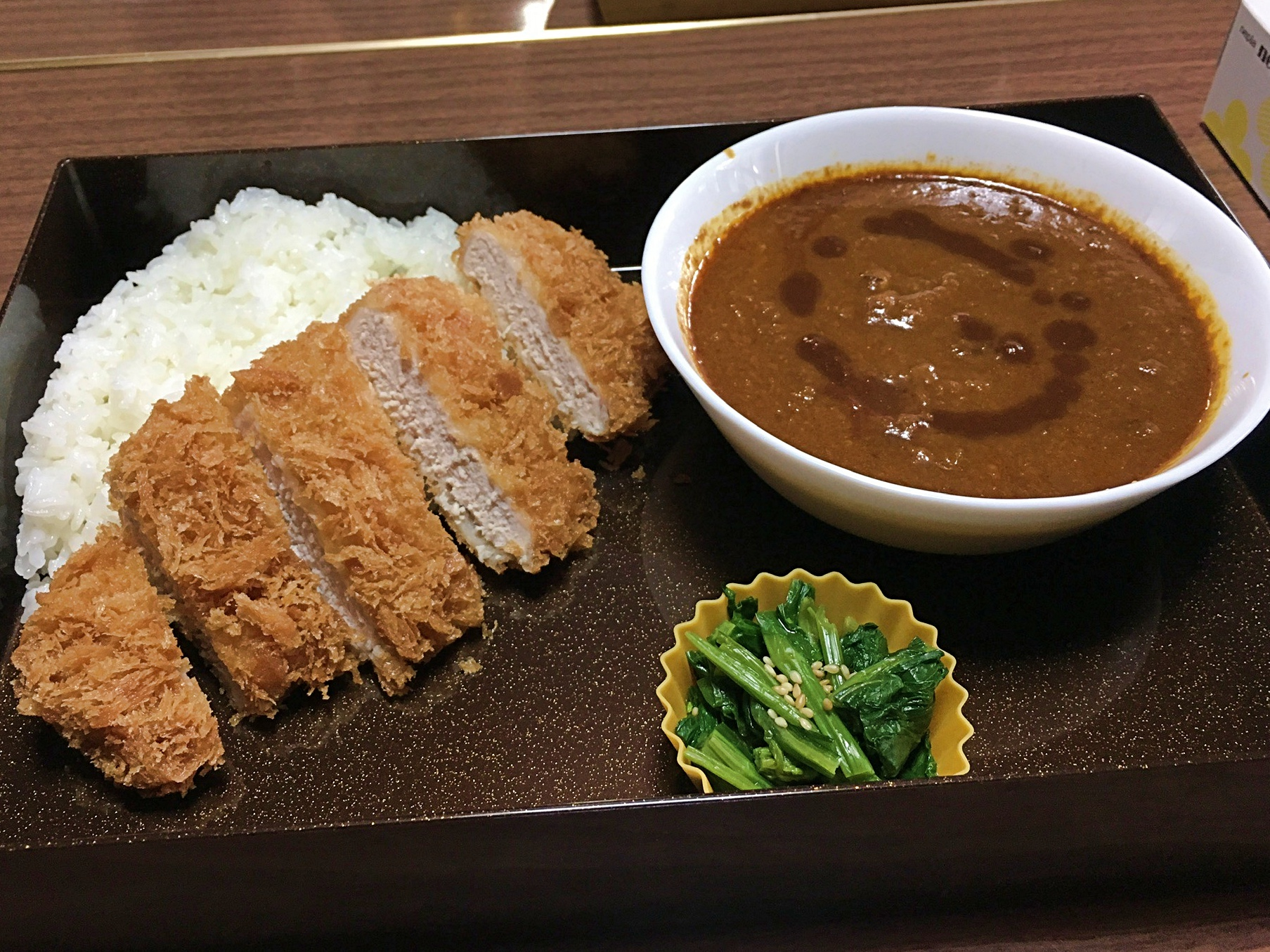 Bento style lunch with steamed white rice, crispy pork tonkatsu cutlet sliced and served with homemade curry sauce with hot chili oil garnish and a small side of blanched chopped spinach.
