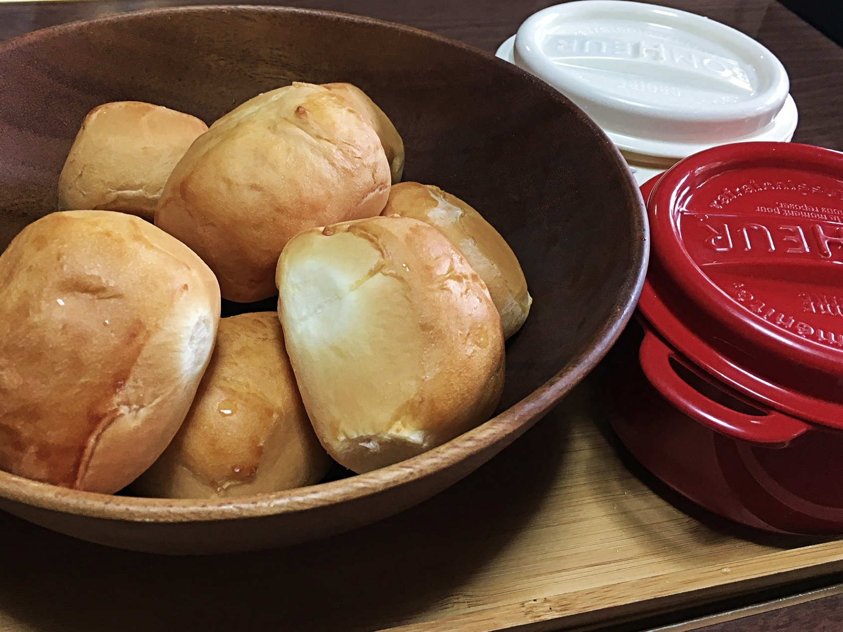 Wooden bowl of sweet bread rolls.