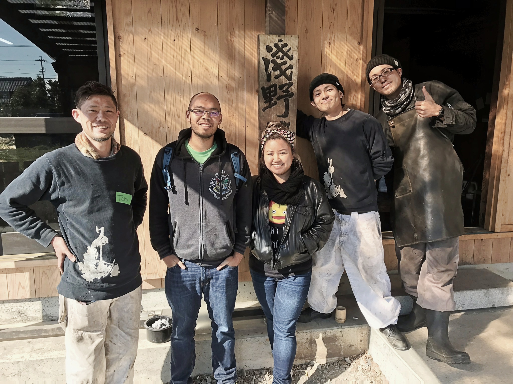 A young couple standing with the master sword-smith and workers at Asano Kajiya located in Gifu, Japan.