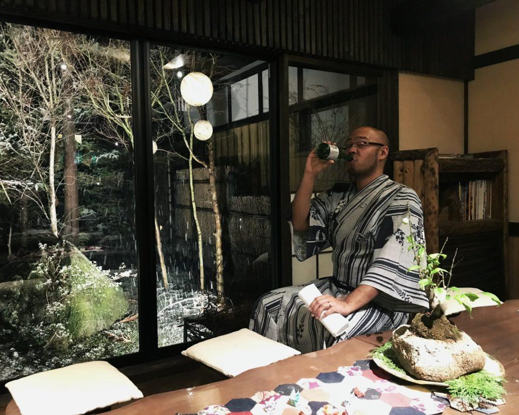 young filipino man drinking sake in a japanese yukata while it is snowing outside Kakurean Hidaji kaiseki at Kakurean Hidaji ryokan in takayama japan