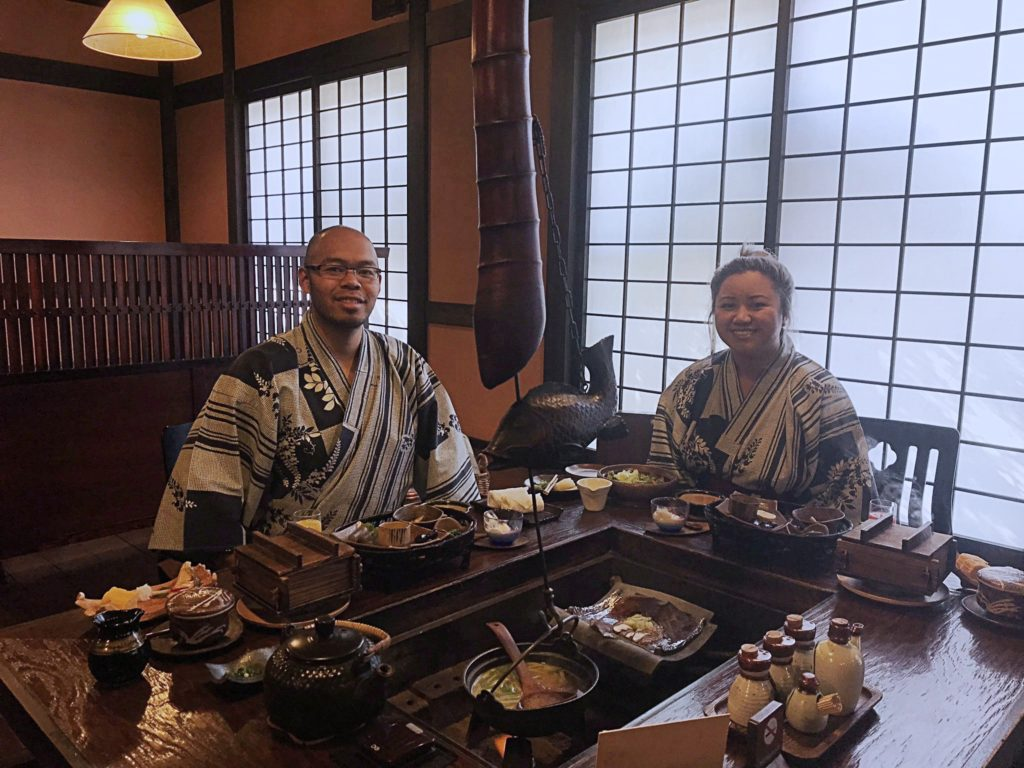 Young man with glasses and woman dressed in yukatas sitting at a japanese style table inlayed with a cooking pit. There are various dishes surrounding them. Kaiseki breakfast at Kakurean Hidaji kaiseki at Kakurean Hidaji ryokan in takayama japan