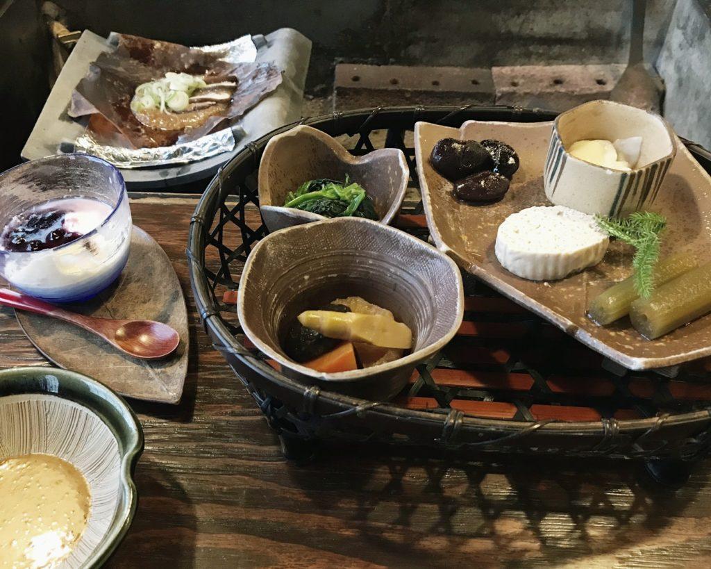 Japanese style breakfast served in a variety of hand crafted ceramic bowls and plates in a basket at Kakurean Hidaji kaiseki at Kakurean Hidaji ryokan in takayama japan