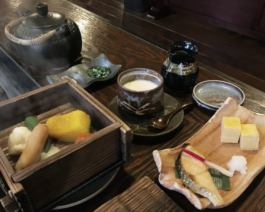 Japanese breakfast with a kettle, a serving box with steamed mountain vegetables, a hand crafted ceramic rectangular plate with grilled fish fillet and two cubes of tofu at Kakurean Hidaji kaiseki at Kakurean Hidaji ryokan in takayama japan