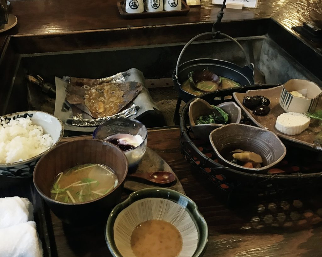 Japanese style breakfast spread with steamed white rice, miso soup, hoba miso, and a variety of fresh local mountain vegetables served in wooden and hand crafted ceramic bowls at Kakurean Hidaji kaiseki at Kakurean Hidaji ryokan in takayama japan