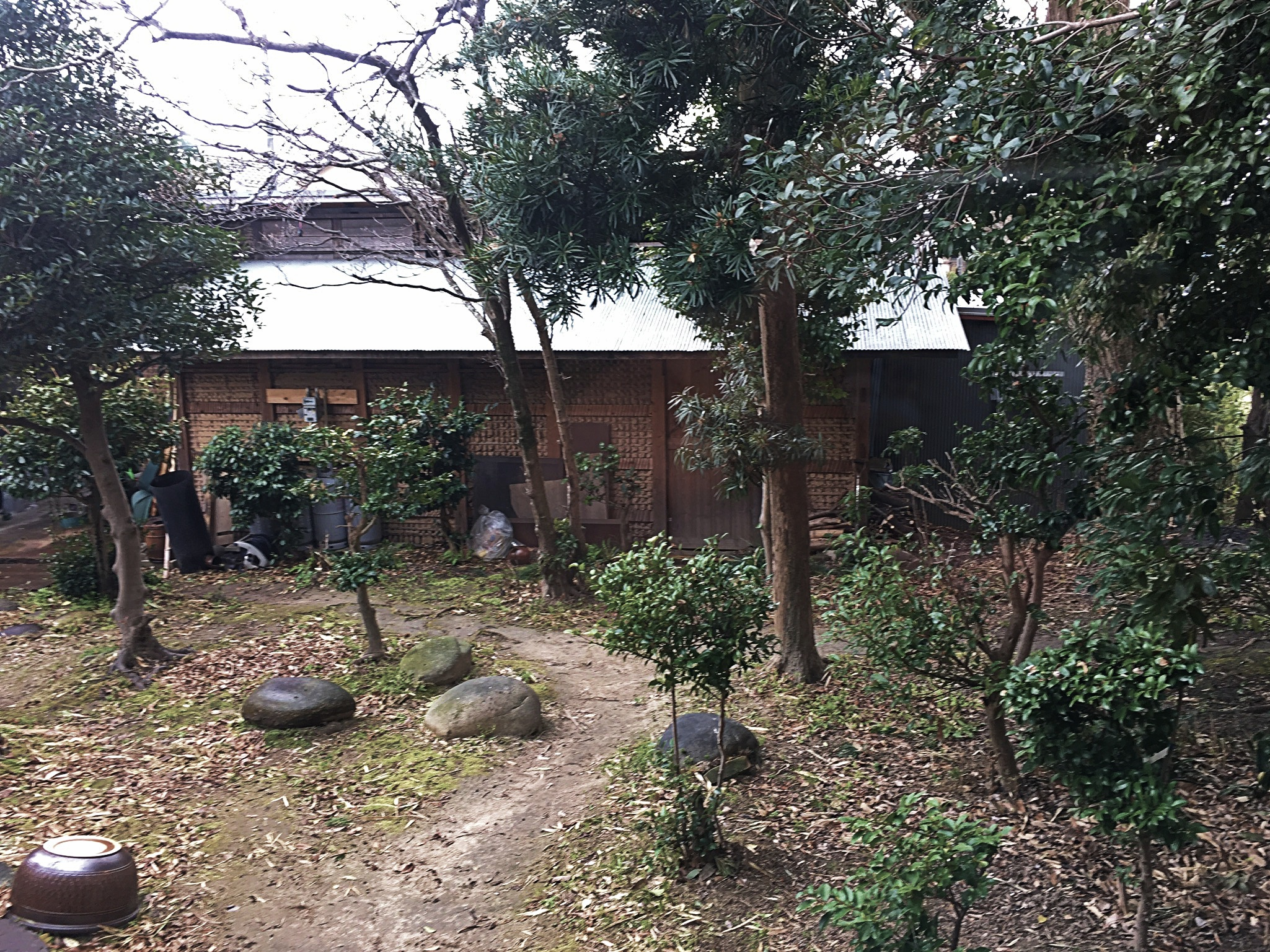 Exterior view of Asano Kajiya. Small dirt path leading to wooden building surrounded by small trees and rocks.